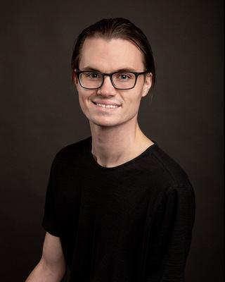 man_headshot_wearing_glasses_darker_background