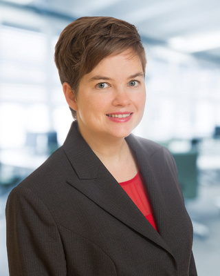Woman with red shirt and jacket for Executive Corporate headshot with blurred office background