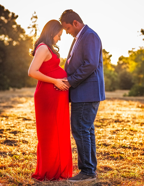 maternity session couple facing each other at sunset