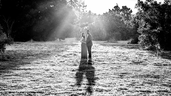 maternity session couple in the middle of big field holding their hands