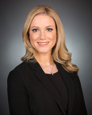 woman with blond hair against gray backdrop studio