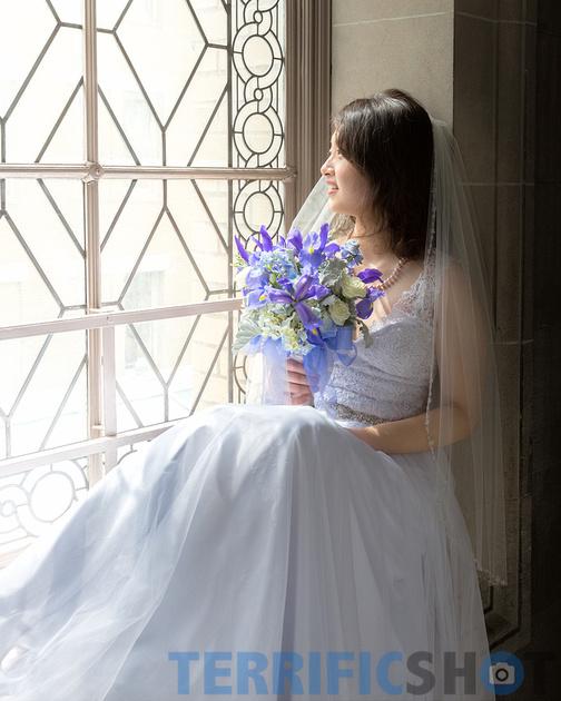 wedding_bride_posing_by_window_with_flower_san_francisco_city_hall