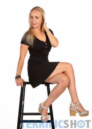 woman_wearing_black_dress_seating_pose_glamour_studio