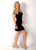 woman_with_blond_hair_standing_and_wearing_black_dress_pose_glamour_studio